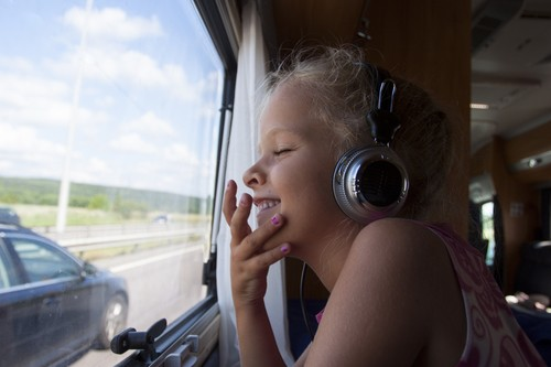 A happy girl with eyes closed sits by window in moving trailer with headphones on